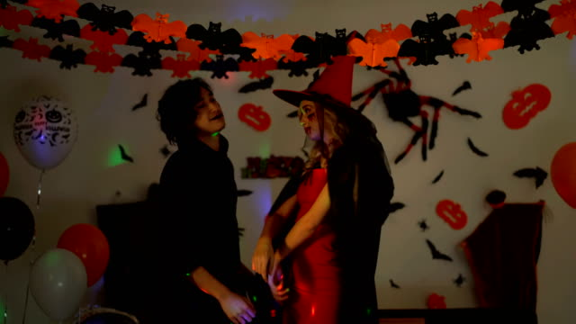 4K Smiling People In Halloween Costumes Celebrating Halloween Party. Young Man And Woman Wearing Halloween Costumes Dancing In The Party