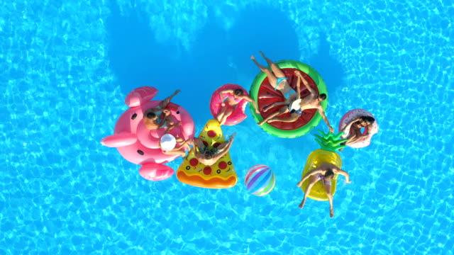 stockvideo's en b-roll-footage met luchtfoto: lachende mensen spelen met een bal op leuke opblaasbare floaties in zwembad - opblaasband