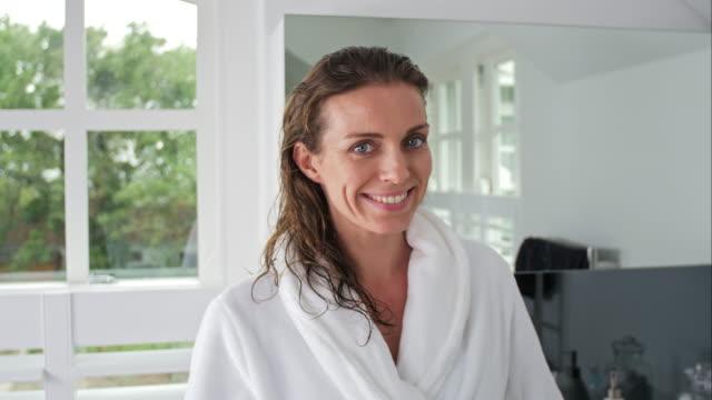 vidéos et rushes de portrait souriant de femme dans la salle de bain - peignoir
