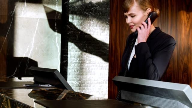 Appel de service de réponse téléphonique souriant concierge assez féminin - Vidéo