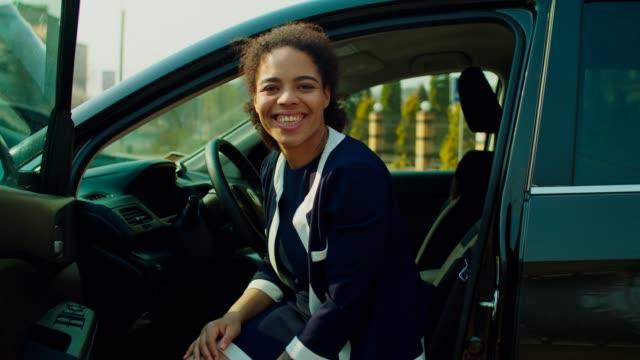 smiling pretty female driver opening car door - sportello d'auto video stock e b–roll