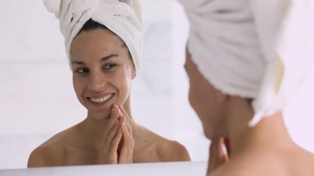 stockvideo's en b-roll-footage met glimlachend mooie jonge vrouw met handdoek op hoofd aanraken gezicht - vrouw schoonmaken