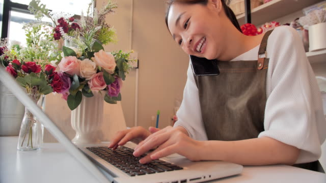 Smiling professional asian woman making a friendly phone call,using computer could be talking to a business contact or a customer.Technology,Lifestyles,Entrepreneurship,Vision,Innovation,Opportunity,Small Business,Leadership,Relationship,Success