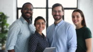 istock Smiling professional multiracial business team colleagues looking at camera 1200288911