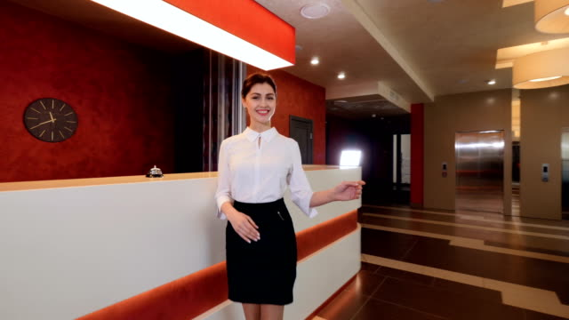 smiling receptionist at hotel reception desk meet guests. 4k. - direttrice video stock e b–roll