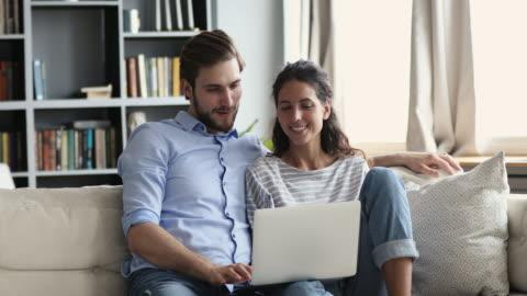 vidéos et rushes de jeune couples détendu de sourire utilisant l'ordinateur portatif à la maison sur le divan - jeune couple