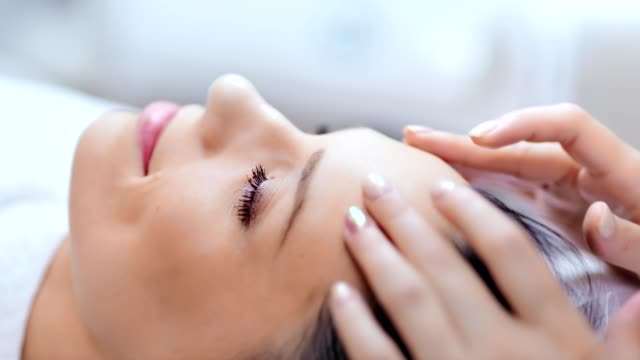smiling relaxing woman enjoying and having good time at massage salon during procedure close-up - spa facial stock videos & royalty-free footage