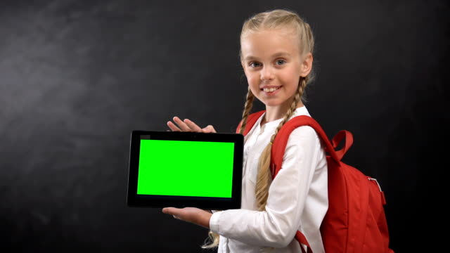 Smiling schoolgirl showing tablet with green screen on camera, educational app