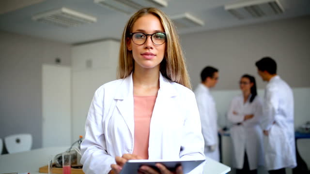 Smiling scientist in laboratory Young smiling female scientist with tablet in the laboratory lab coat stock videos & royalty-free footage