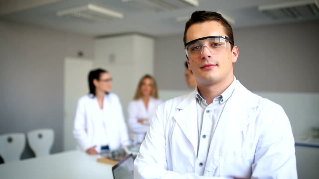 Smiling scientist in laboratory Young smiling male scientist in the laboratory lab coat stock videos & royalty-free footage
