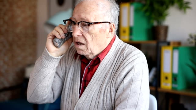 Smiling senior adult talking on the phone and laughing video