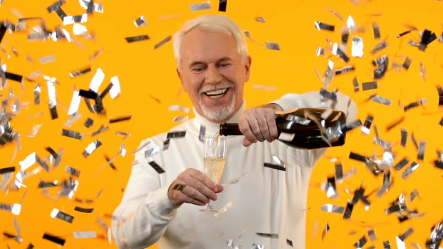 Smiling senior man celebrating holiday, pouring champagne under falling confetti