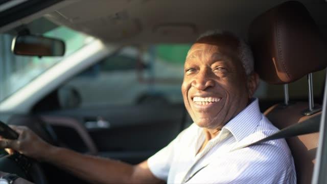 lächelnder senior mann fährt ein auto und schaut in die kamera - brasilianischer abstammung stock-videos und b-roll-filmmaterial