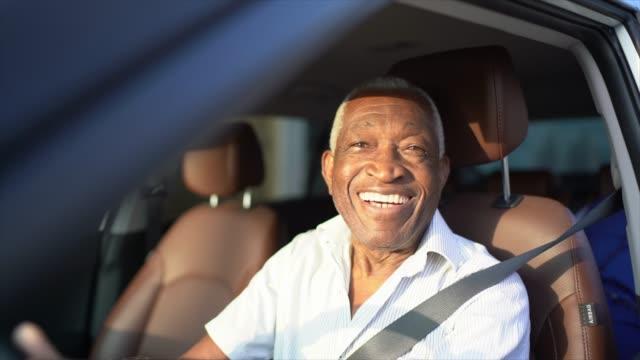 улыбающийся старший человек за рулем автомобиля и глядя на камеру - бразилец парду стоковые видео и кадры b-roll