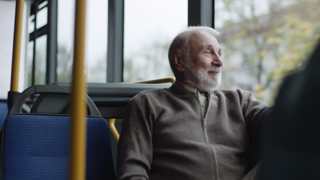 Smiling senior man riding on a bus video