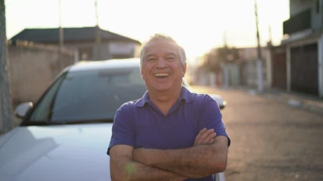 vídeos de stock, filmes e b-roll de homem sênior de sorriso que está na frente de seu carro - povo brasileiro