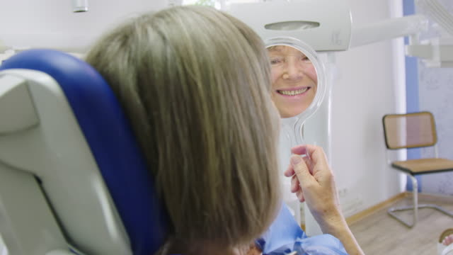 Smiling senior woman holding hand mirror in clinic
