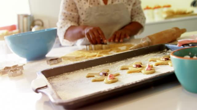 Smiling senior woman preparing cookies in kitchen 4k Smiling senior woman preparing cookies in kitchen at home 4k gingerbread man stock videos & royalty-free footage