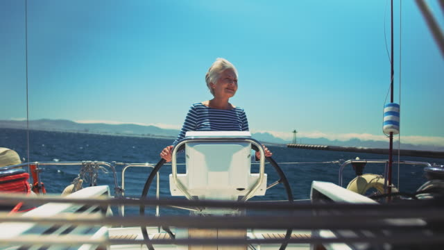 Video Smiling senior woman steering boat in vacation