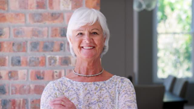 Smiling senior woman walks into focus looking to camera Smiling senior woman walks into focus looking to camera image focus technique stock videos & royalty-free footage
