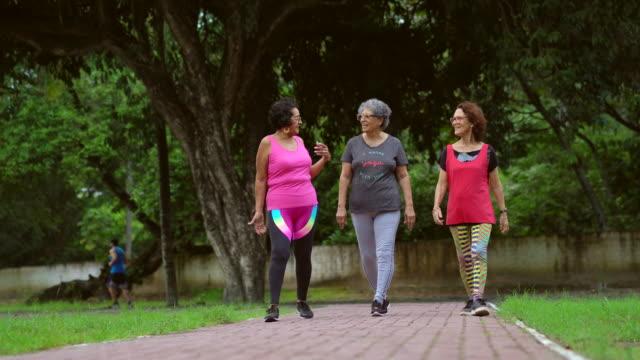 vidéos et rushes de femmes âgées de sourire faisant jogging dans le stationnement - relaxation