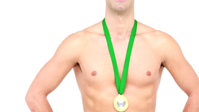 atleta a petto nudo sorridente con medaglia mostrando pollice alzato - mani sui fianchi video stock e b–roll