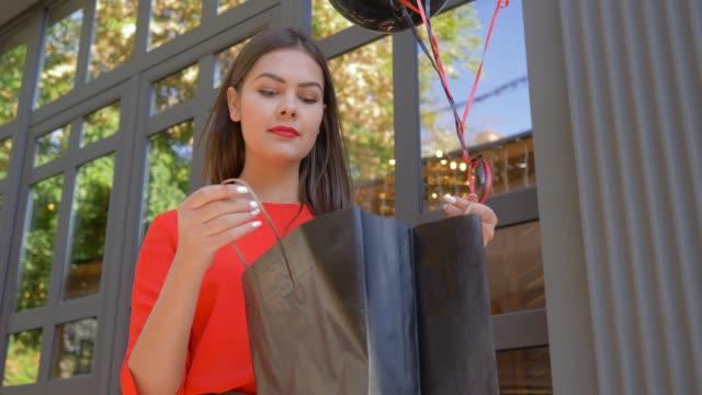 vídeos y material grabado en eventos de stock de niña sonriente comprador asoma en bolsa de papel con nuevas compras de tienda de moda durante la venta en negro el viernes - black friday sale