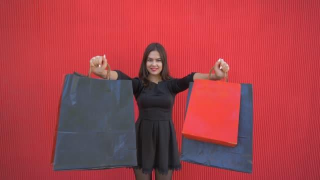 vídeos y material grabado en eventos de stock de sonriente mujer shopper hizo muchas compras en temporada de descuentos en black friday y levanta los paquetes en las manos - black friday sale