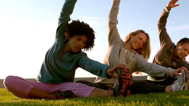 Smiling sporty women stretching during fitness class video