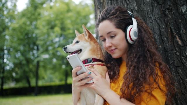 köpekile parkta akıllı telefon kullanarak kulaklık müzik zevk gülümseyen öğrenci - kulaklık seti ses ekipmanı stok videoları ve detay görüntü çekimi