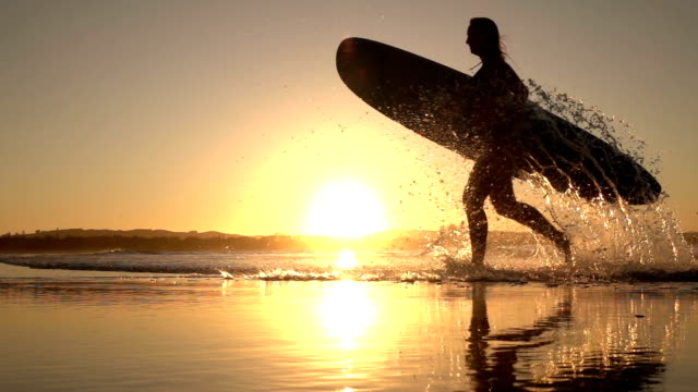 SLOW MOTION: Smiling surfer girl running out of ocean splashing water at sunset video