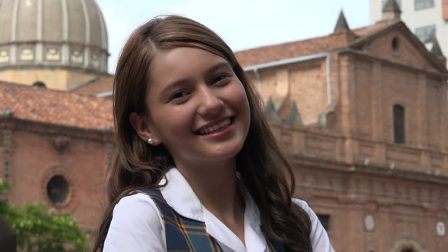 vídeos de stock, filmes e b-roll de menina adolescente sorridente, perto de igreja - 16 17 anos