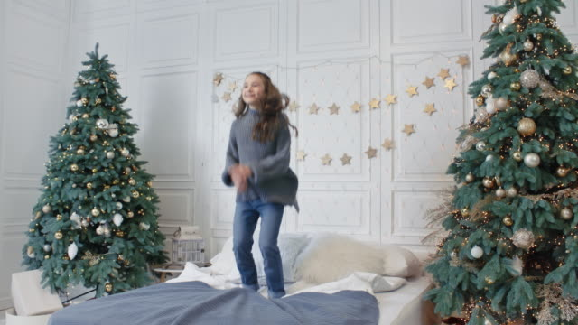 Smiling teenage girl jumping bed in home. Happy kid having party in bedroom Smiling teenage girl jumping bed in home. Happy kid having party in bedroom. Cheerful daughter relaxing on new year vacation jumping in double bed. double bed stock videos & royalty-free footage