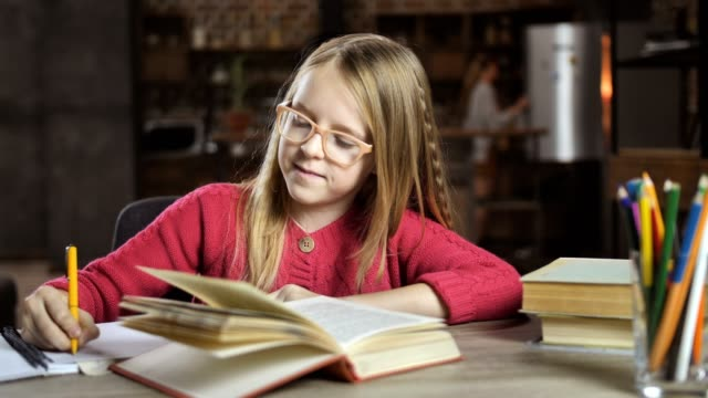 Smiling teenage girl studying lessons at home video