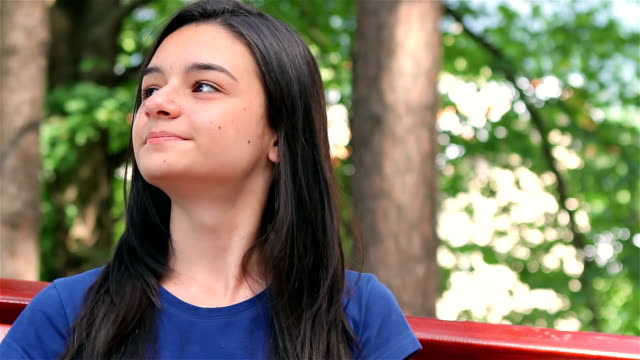 Smiling teenager girl relaxing in the park video