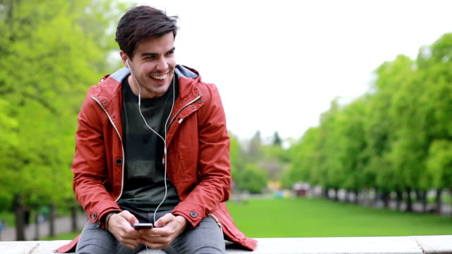Smiling teenager smart phone texting outdoors video