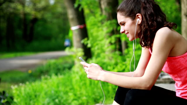 Smiling teenager with smart phone texting outdoors video