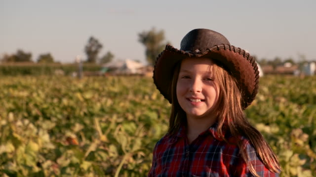 Smiling ten years old American farm girl looking at the camera wearing a cowboy hat