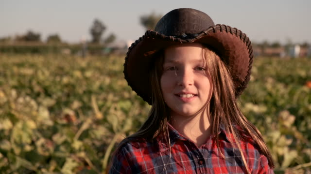 smiling ten years old american farm girl looking at the camera wearing a cowboy hat - solo una bambina femmina video stock e b–roll
