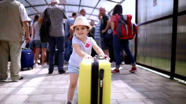 smiling toddler pushing her coffer on a airport - pasażer filmów i materiałów b-roll