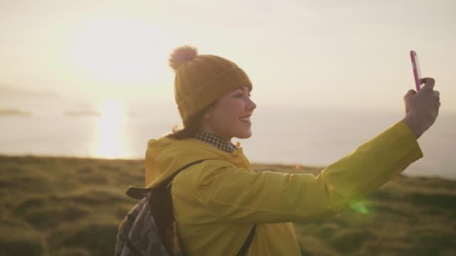 lächelnde touristen nehmen selfie mit smartphone auf berg über dem meer - freizeitaktivität im freien stock-videos und b-roll-filmmaterial