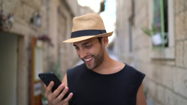 Smiling tourist using mobile phone on the street