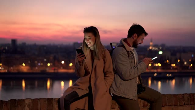 Smiling tourists using cellphones Smiling tourist couple occupied with smart phones ignoring each other on their vacation. back to back stock videos & royalty-free footage