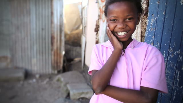 Smiling township girl portrait Video portrait of a cute African township girl smiling and giggling at camera poverty stock videos & royalty-free footage