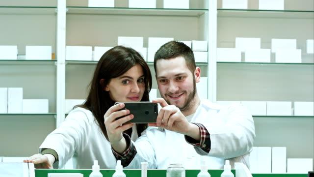 ler två apotekspersonal tar selfie i apotek - hospital studio bildbanksvideor och videomaterial från bakom kulisserna