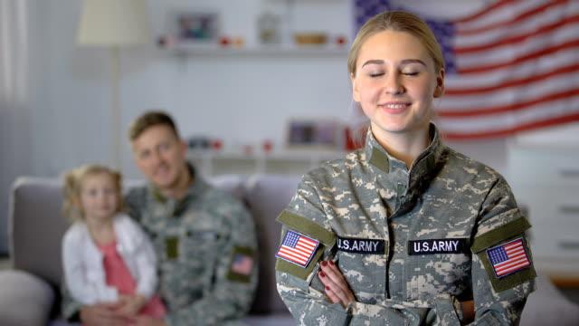 vidéos et rushes de sourire de femme de soldat américain regardant l'appareil-photo, mari et fille admirant la maman - admiration