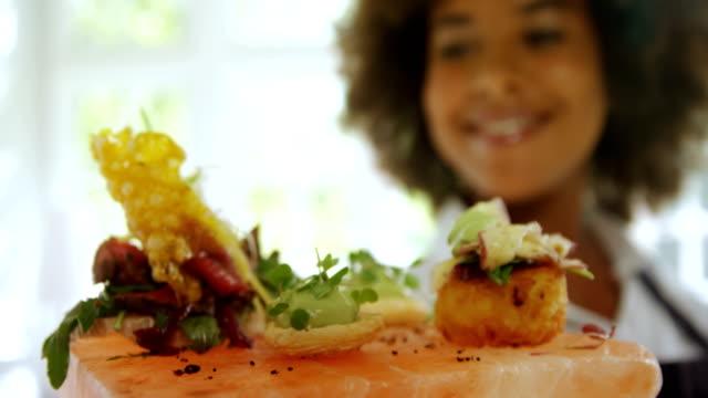 Smiling waitress holding food tray