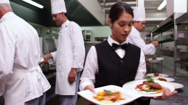 Smiling waitress showing two dishes to camera Smiling waitress showing two dishes to camera in a commercial kitchen wait staff stock videos & royalty-free footage