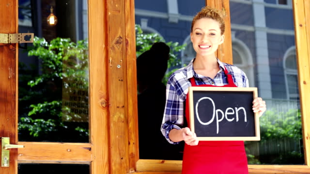 smiling waitress standing outside door with open sign board in cafe - open sign stock videos & royalty-free footage