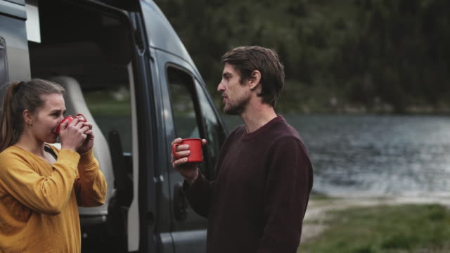 Smiling woman and man drinking coffee by motor van